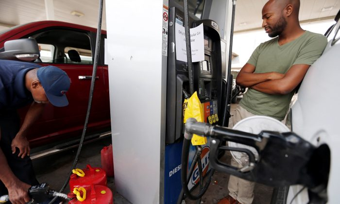 Cains Lawrence (L), and Derrick Washington fill up gasoline cans and their vehicles at the Fuel City service station in the aftermath of Hurricane Harvey, in Dallas, Texas, U.S., September 1, 2017.  (Reuters/Brandon Wade)