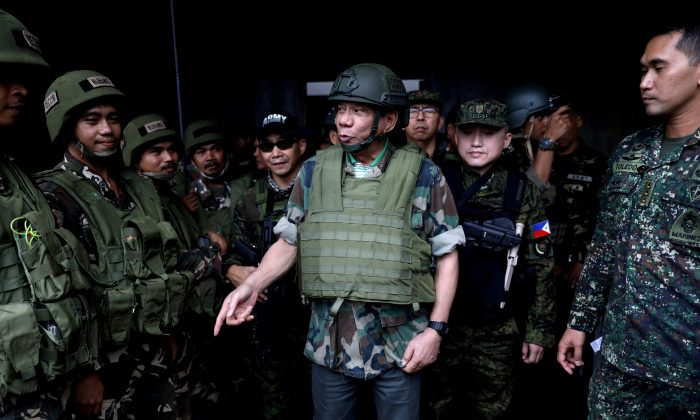 FILE PHOTO: Philippine President Rodrigo Duterte wears a bulletproof vest and a helmet as he gives a pep talk to troops fighting the extremist Maute group in Marawi, Philippines August 24, 2017. Picture taken August 24, 2017.  Presidential Palace/Handout via (Reuters/File Photo)