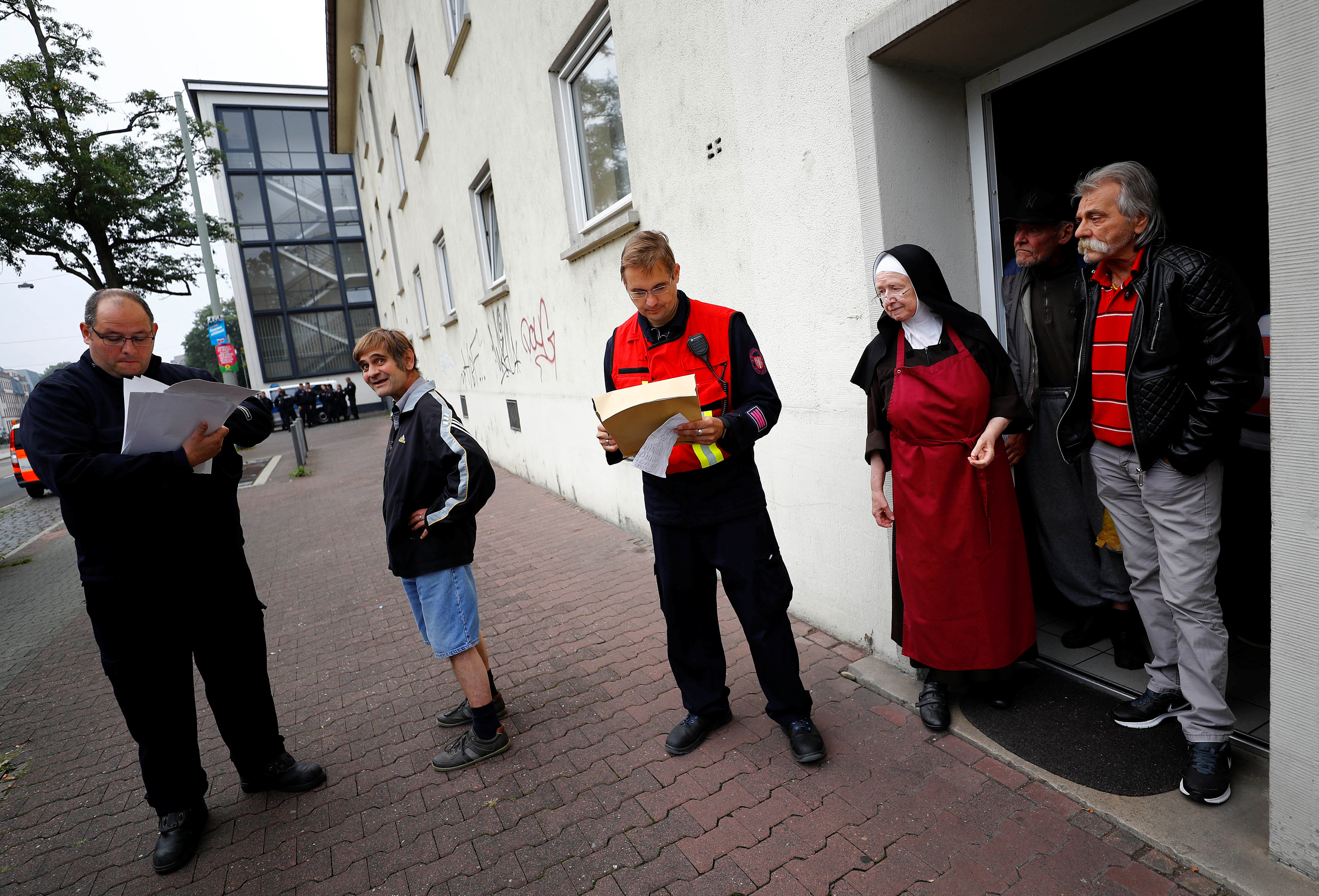 Sister Sigrid (3rdR) talks to firefighters and police officers as she observes the evacuation of her nursery home for homeless people as 60,000 people in Germany's financial capital are about to evacuate the city while experts defuse an unexploded British World War Two bomb found during renovations on the university's campus in Frankfurt, Germany, on Sept. 3, 2017.  (REUTERS/Kai Pfaffenbach)
