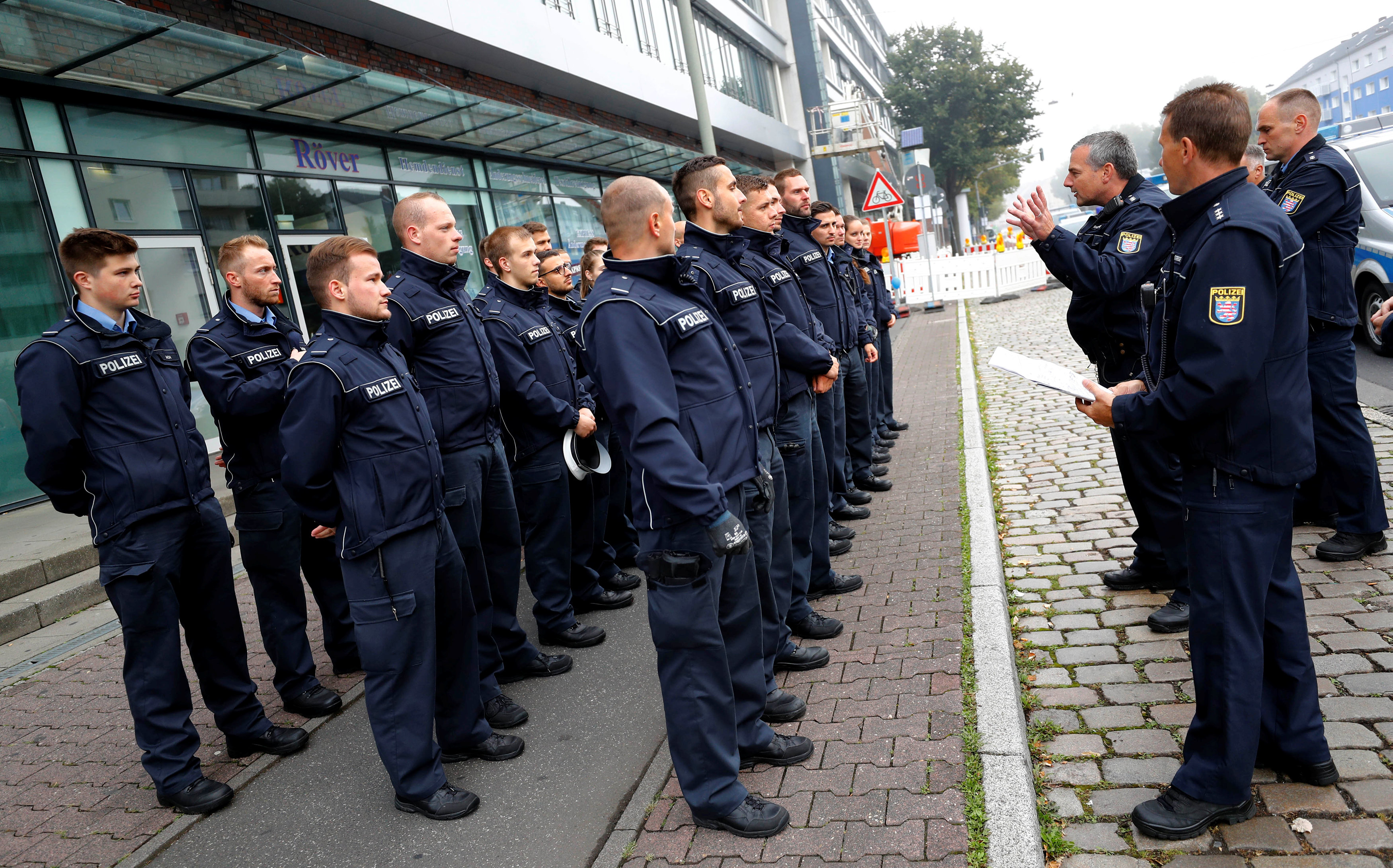 Police officers get their instructions as 60,000 people in Germany's financial capital are about to evacuate the city while experts defuse an unexploded British World War Two bomb found during renovations on the university's campus in Frankfurt, Germany on Sept. 3, 2017.  (REUTERS/Kai Pfaffenbach)