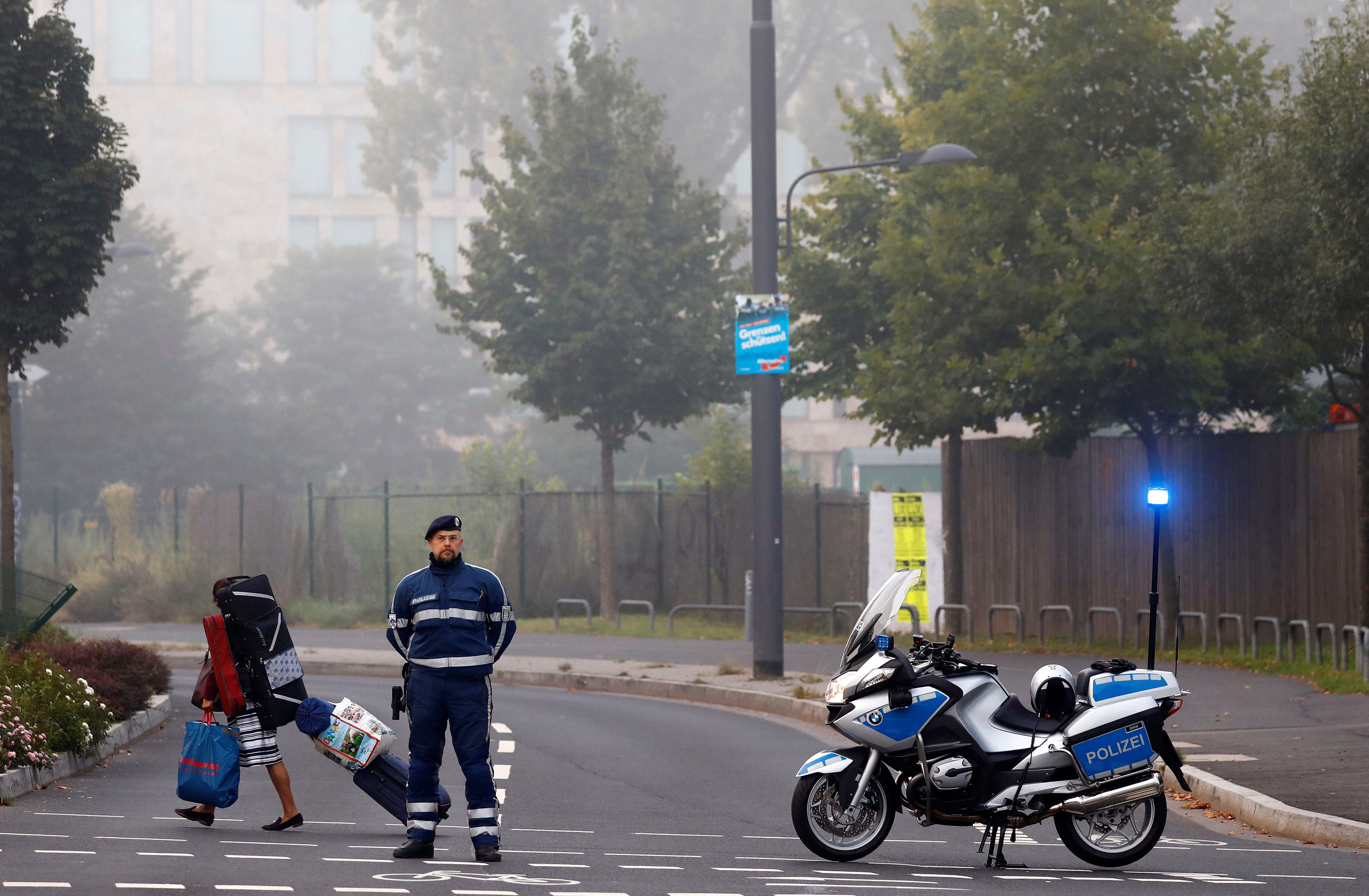 A woman carries her belongings walking past a police officer as some 60,000 people in Germany's financial capital are about to evacuate the city while experts defuse an unexploded British World War Two bomb found during renovations on the university's campus in Frankfurt, Germany on Sept. 3, 2017.  (REUTERS/Kai Pfaffenbach)