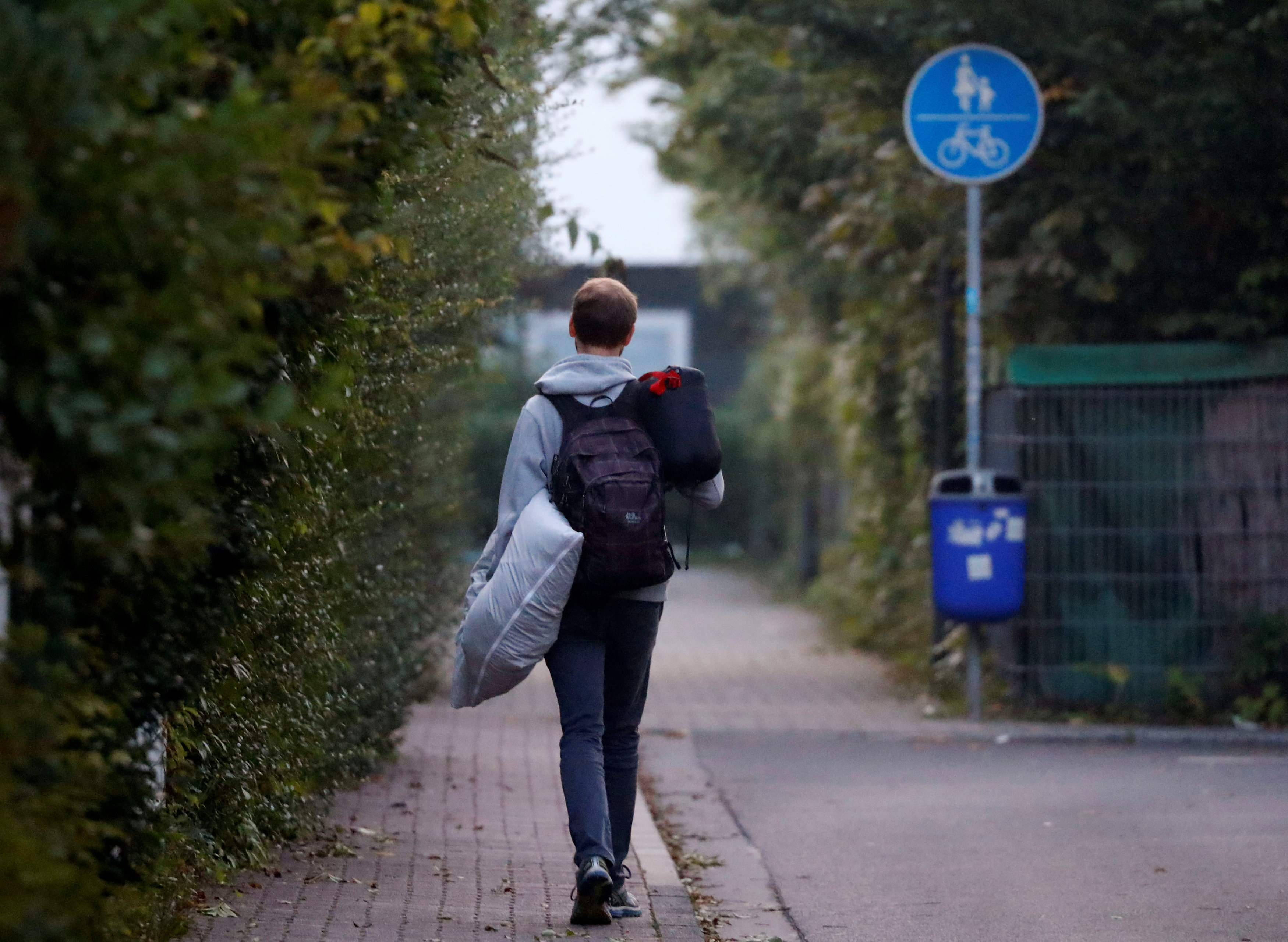 A young man carries his pillow and a sleeping bag as some 60,000 people in Germany's financial capital are about to evacuate the city while experts defuse an unexploded British World War Two bomb found during renovations on the university's campus in Frankfurt, Germany on Sept. 3, 2017.  (REUTERS/Kai Pfaffenbach)