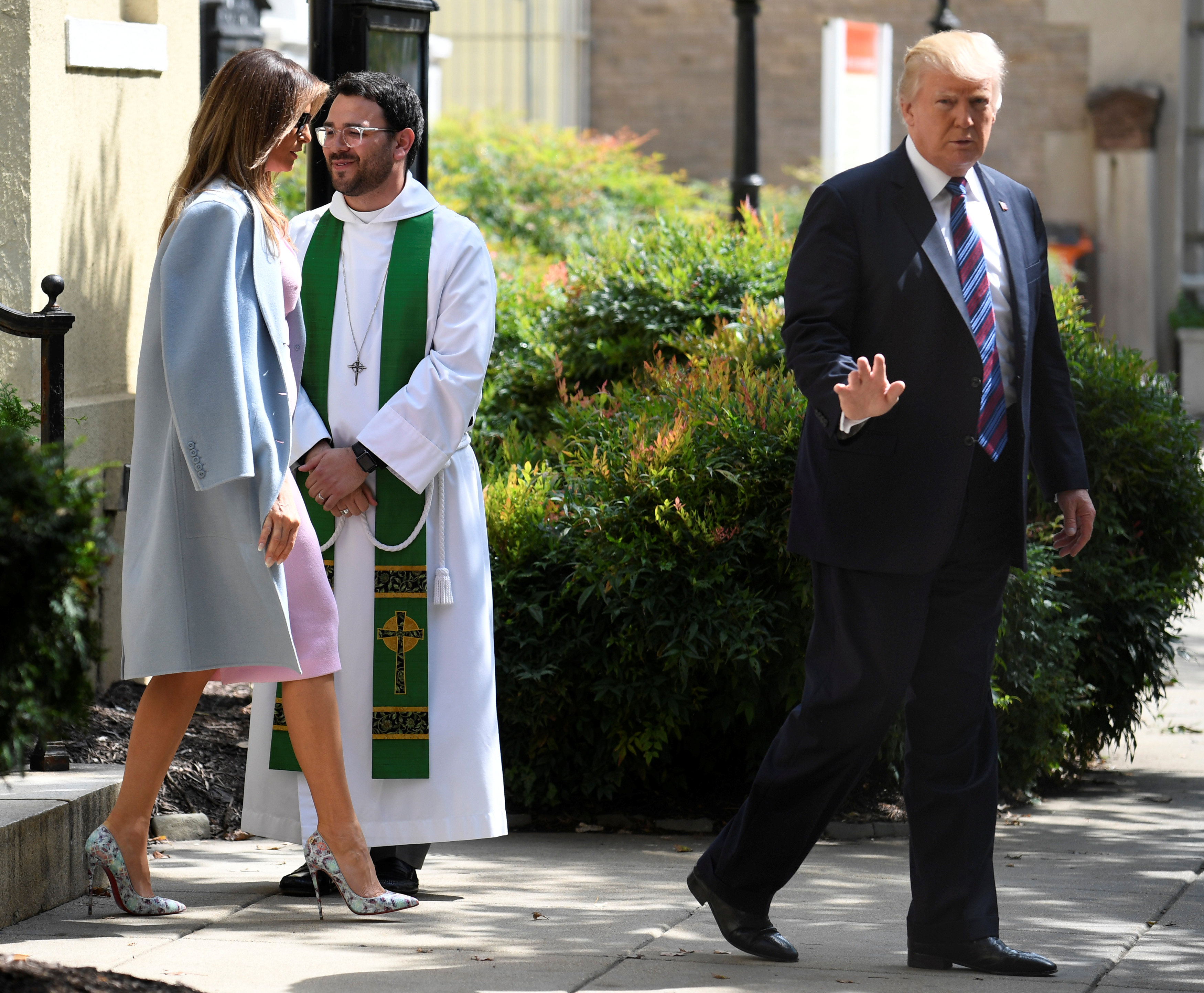 "President Donald Trump waves to the press, as he departs St. John's Episcopal Church and Assistant Rector D. Andrew Olivo, (C), with First Lady Melania Trump after they attended services for a national ""Day of Prayer"", for victims of the Hurricane Harvey flooding in Texas, in Washington on Sept.3, 2017. (REUTERS/Mike Theiler)"