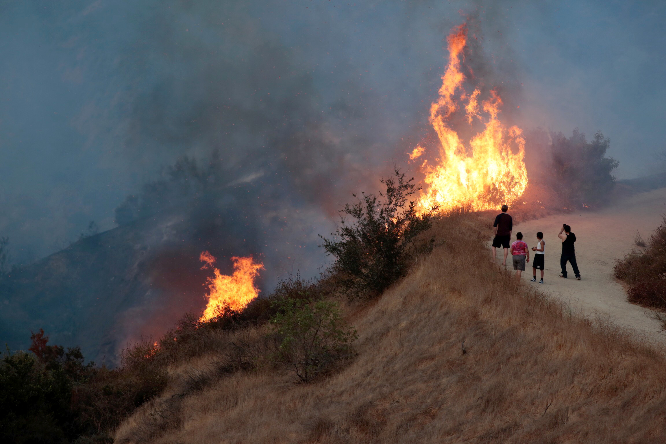People look on at the La Tuna Canyon fire over Burbank. (REUTERS/Kyle Grillot)