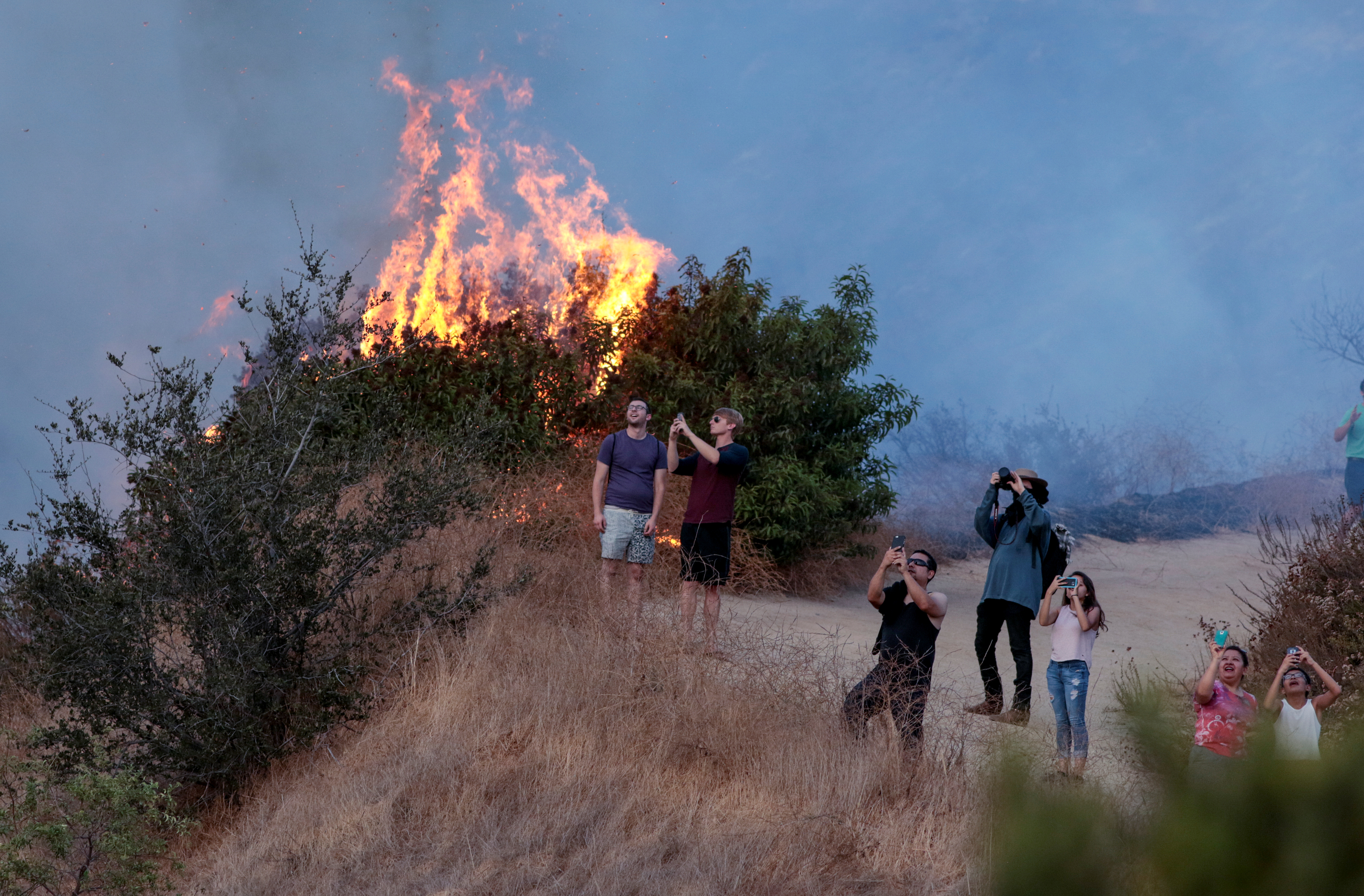 Spectators watch a helicopter fly over the La Tuna Canyon fire over Burbank. (REUTERS/ Kyle Grillot)