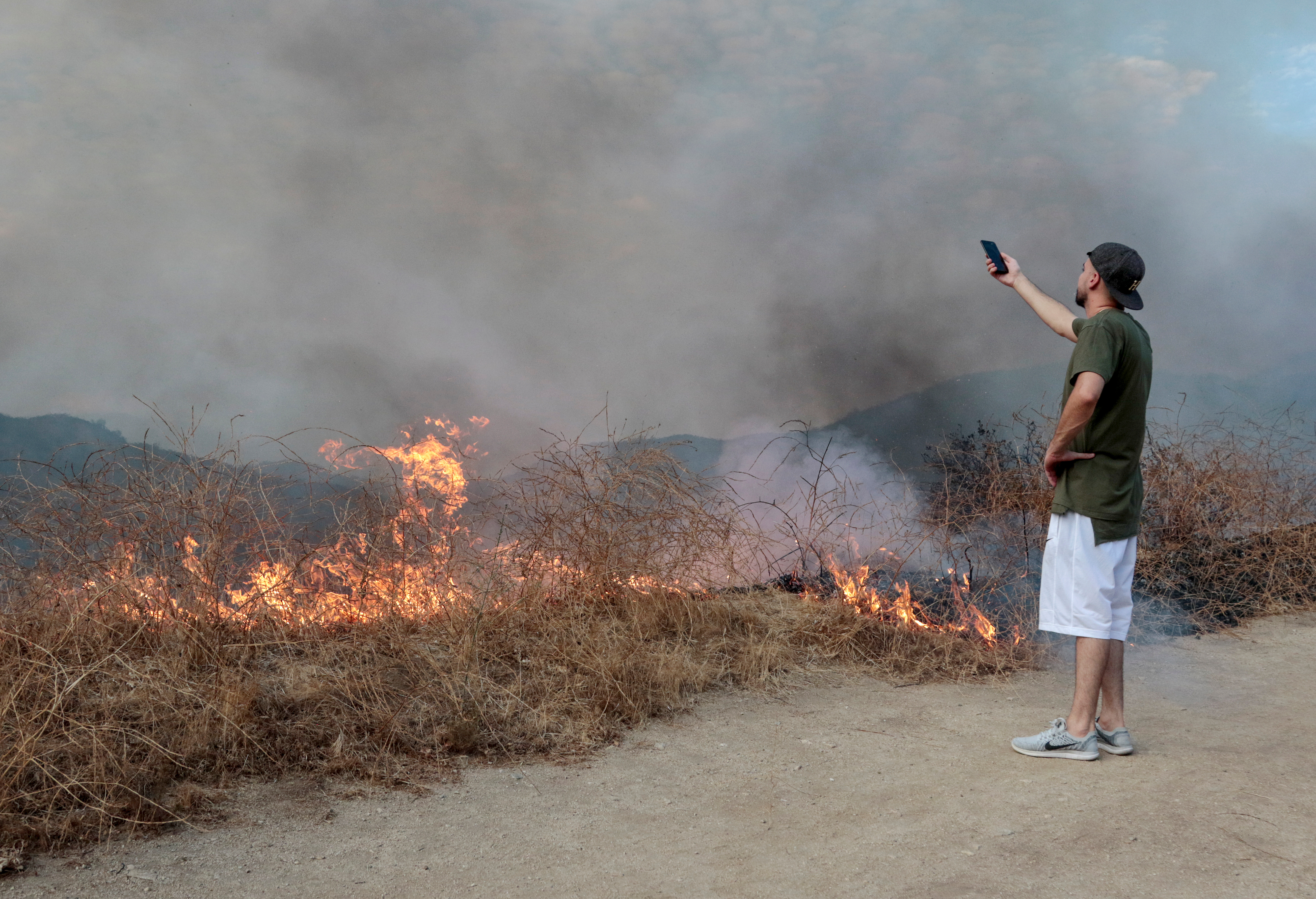 A spectator films the La Tuna Canyon fire over Burbank. (REUTERS/ Kyle Grillot)