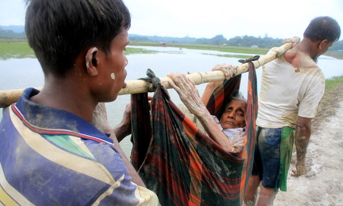 Rohingya refugees carry an old woman from Rakhine state in Myanmar along a path near Teknaf in Bangladesh on September 3, 2017. (R. ASAD/AFP/Getty Images)