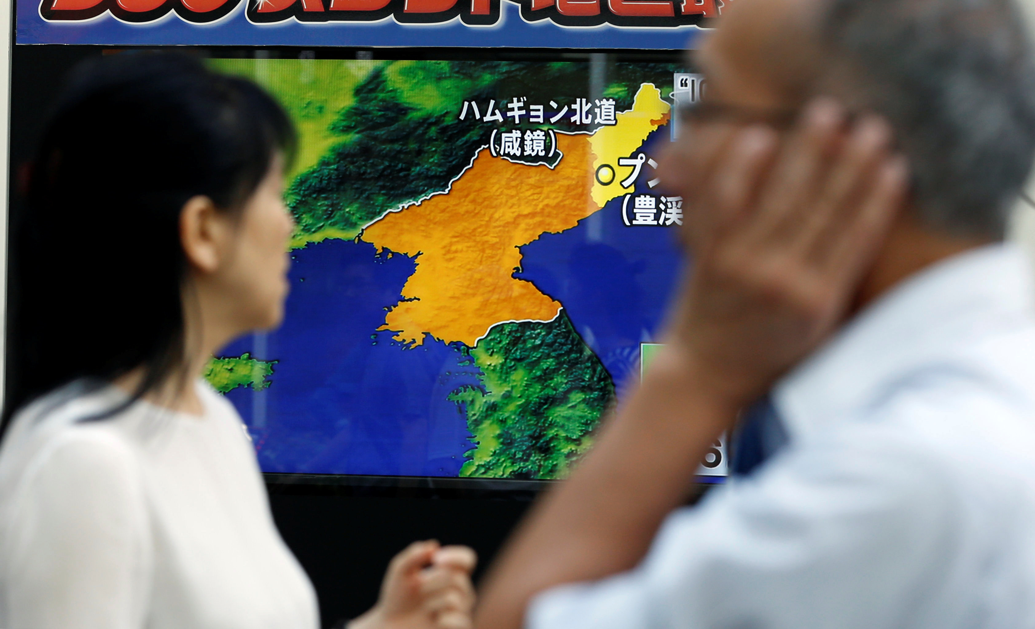 People walk past a street monitor showing a news report about North Korea's nuclear test, in Tokyo, Japan on Sept. 3, 2017. (REUTERS/Toru Hanai)