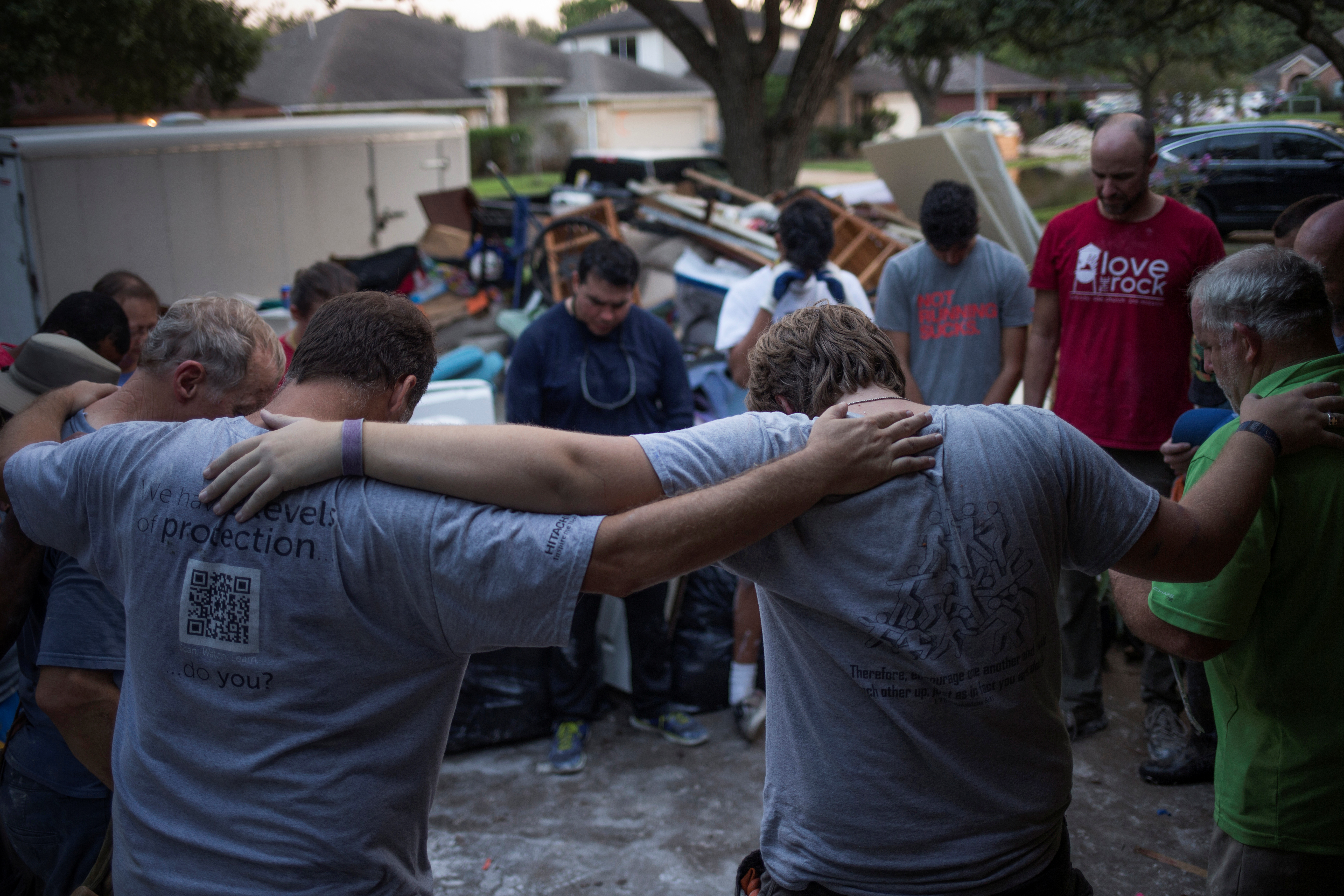 Samaritans  pray after helping clear furniture from the flooded house of a neighbor in the aftermath of Tropical Storm Harvey in Houston, Texas on Sept. 3, 2017. (REUTERS/Adrees Latif)