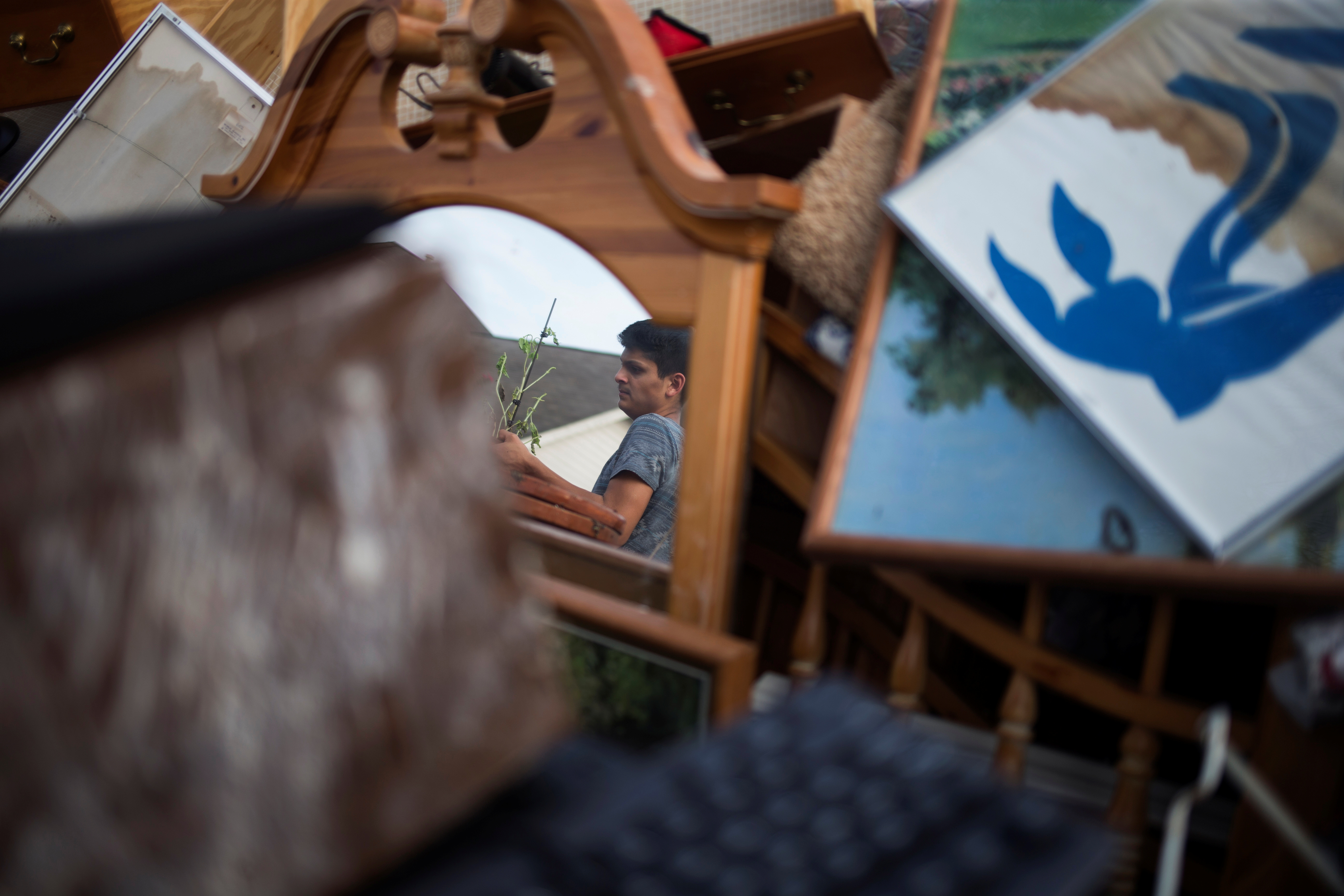 Isaac Zermeno is reflected in a mirror as he helps discard furniture from the house of a neighbor who was left flooded from Tropical Storm Harvey in Houston, Texas on Sept. 3, 2017. (REUTERS/Adrees Latif)