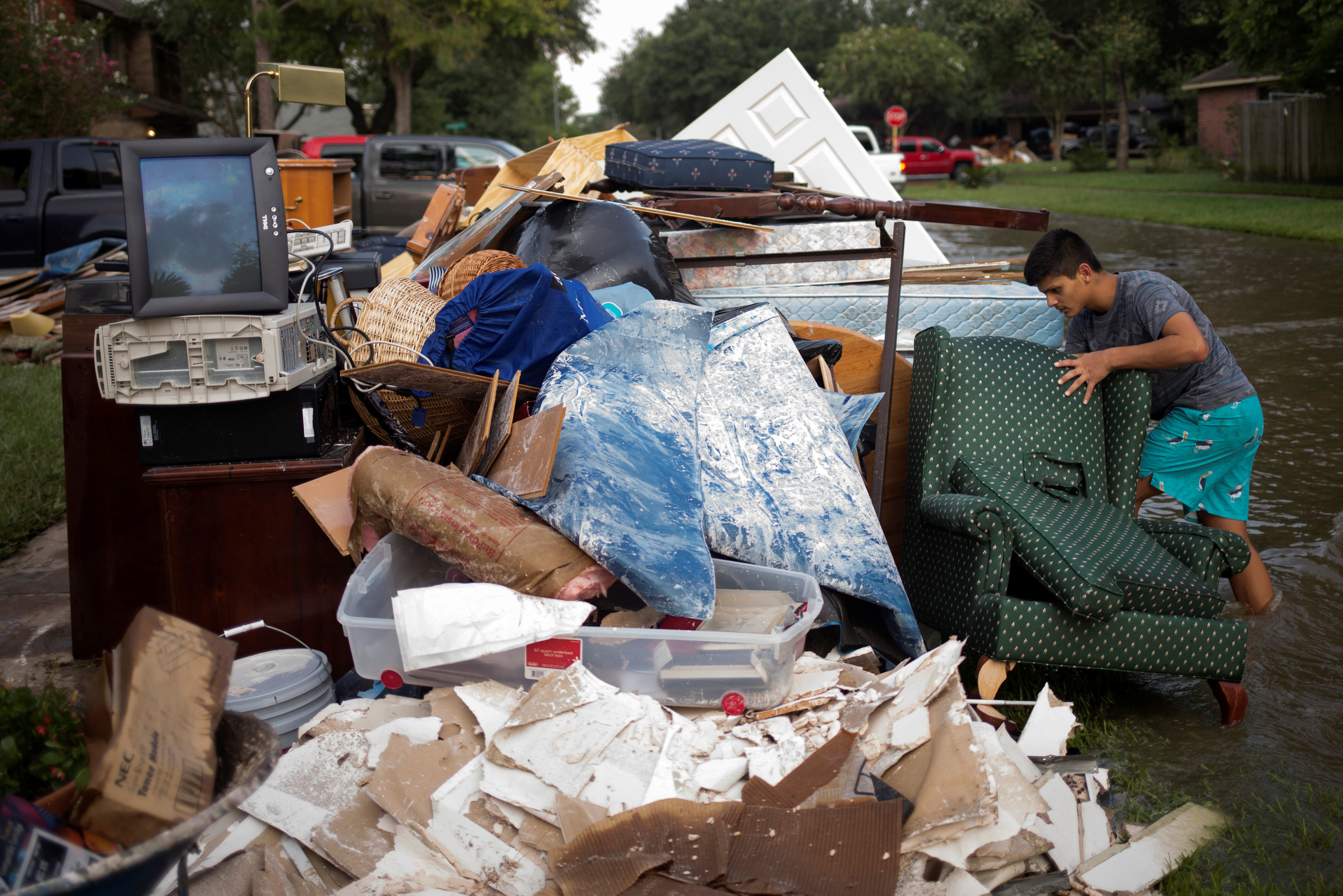 Isaac Zermeno discard furniture from the house of a neighbor who was left flooded from Tropical Storm Harvey in Houston, Texas on Sept. 3, 2017. (REUTERS/Adrees Latif)
