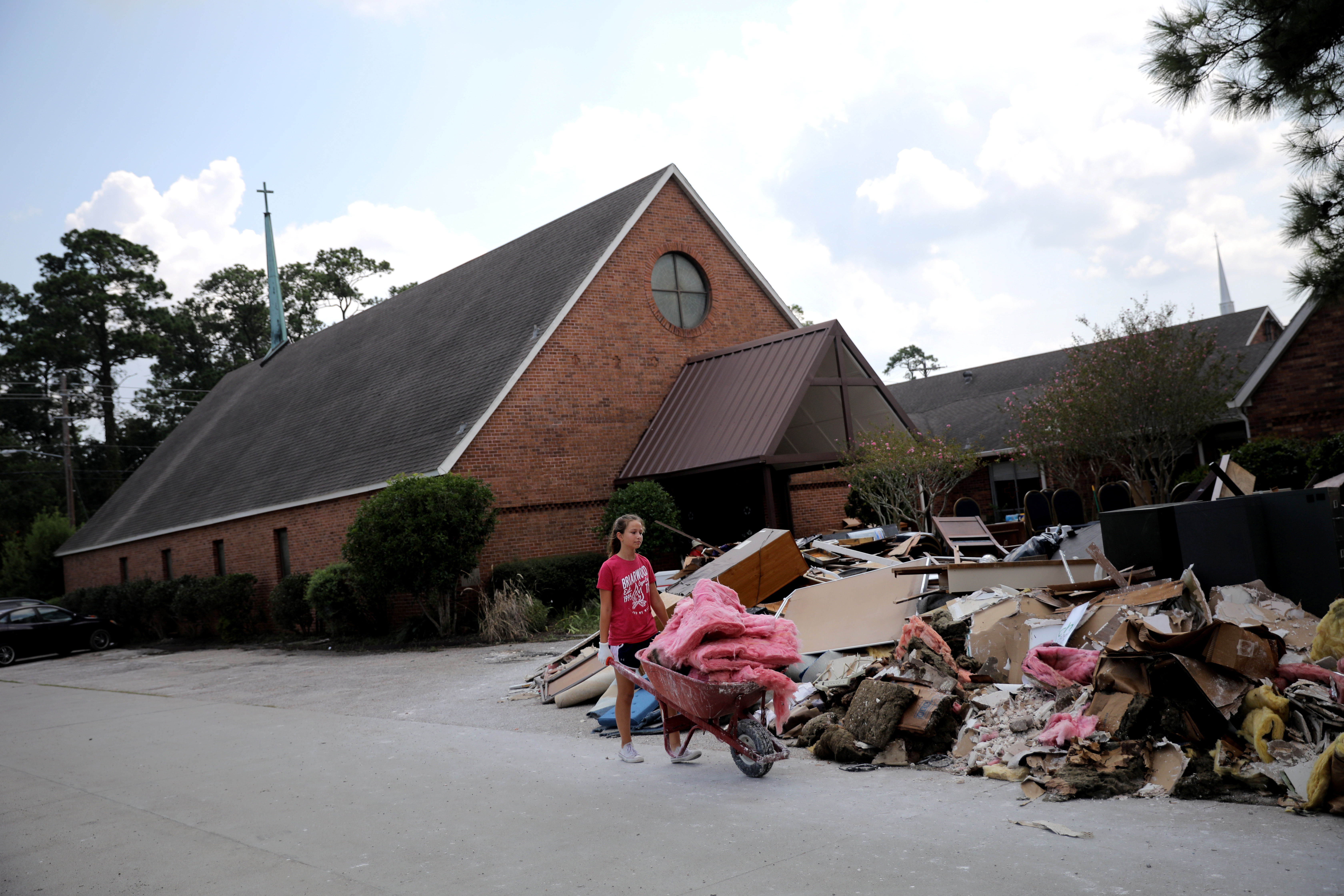 A volunteer helps clean up the damage at a Lutheran church in Dickinson, Texas. (REUTERS/Carlos Barria)