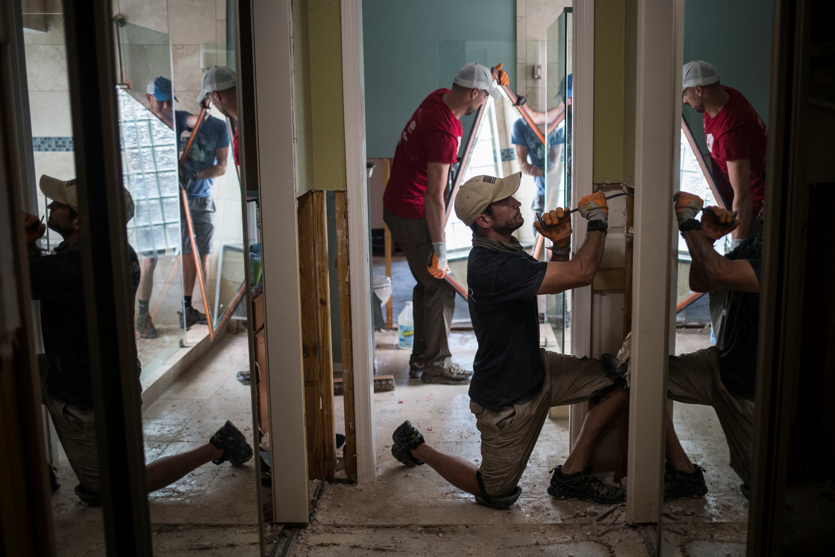 Ben Hyman and other samaritans help clear debris from the house of a neighbor which was left flooded from Tropical Storm Harvey in Houston, Texas on Sept. 3, 2017. (REUTERS/Adrees Latif)