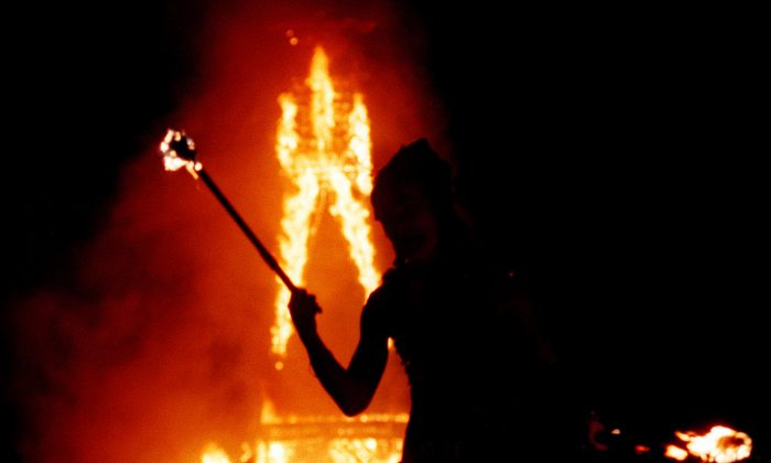 A dancer juggles fire as a 52-foot tall wooden man as it goes up in flames September 2, 2000 during the15th annual Burning Man festival in the Black Rock Desert near Gerlach, Nevada. (David McNew/Newsmakers)
