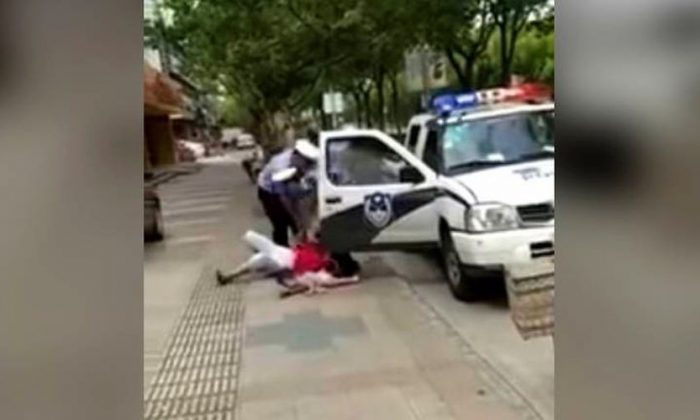 Screenshot of the police officer knocking down the woman with her child (YouTube / screenshot)