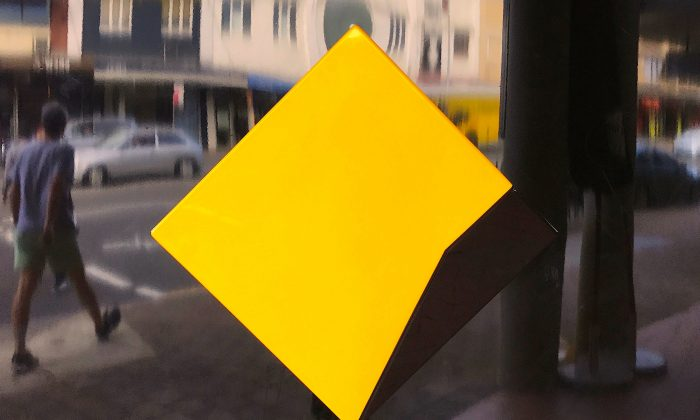 FILE PHOTO - A pedestrian walks past a logo for the Commonwealth Bank located outside a branch in Sydney, Australia, May 8, 2017. (Reuters/David Gray)