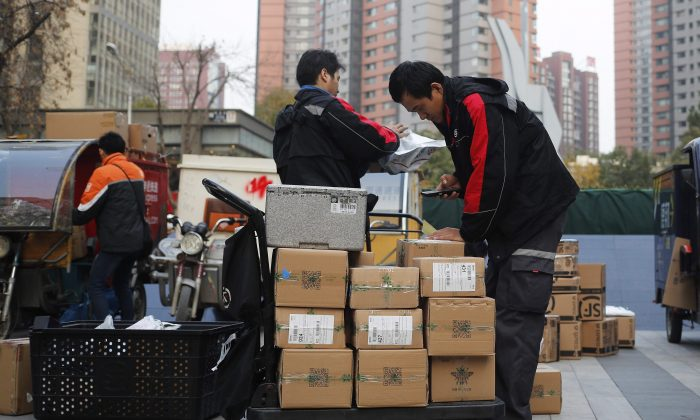 """Delivery workers sort parcels for their customers in Beijing, China on """"Singles Day,"""" a holiday that has grown into the world's busiest day for e-commerce, Nov. 11, 2016. (AP Photo/Andy Wong)"""