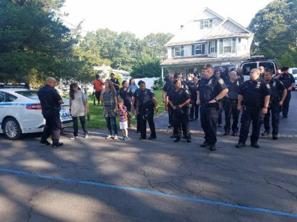 New York police officers from a precinct in the Bronx accompany Austin, son of slain Sgt. Paul Tuozzolo, to his first day of school.  (NYPD/Twitter)