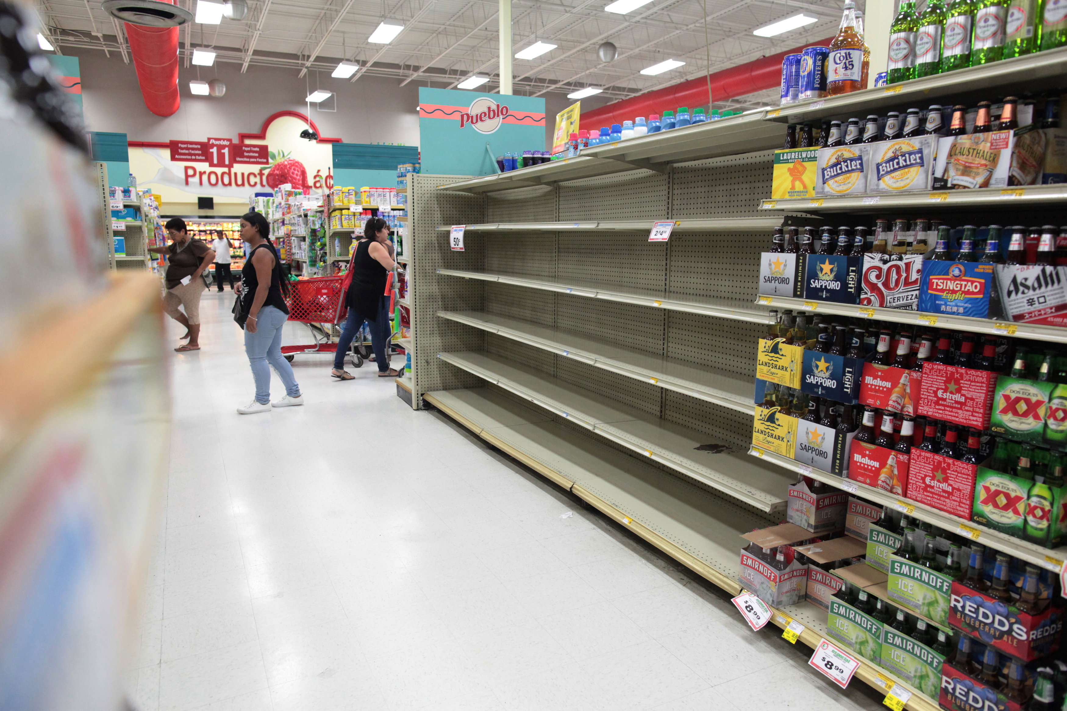 Customers walk near empty shelves that are normally filled with bottles of water after Puerto Rico Governor Ricardo Rossello declared a state of emergency in preparation for Hurricane Irma, in San Juan, Puerto Rico on Sept. 4, 2017. (REUTERS/Alvin Baez)