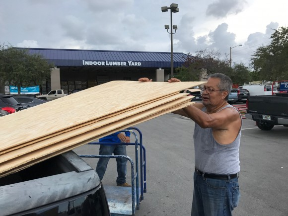 Jerry Garcia, 70, a retired mechanic, loads one of the 20 sheets of plywood he is taking home to prepare for Hurricane Irma at a home supply store in Oakland Park, Florida, U.S., September 5, 2017.    (REUTERS/Bernie Woodall)