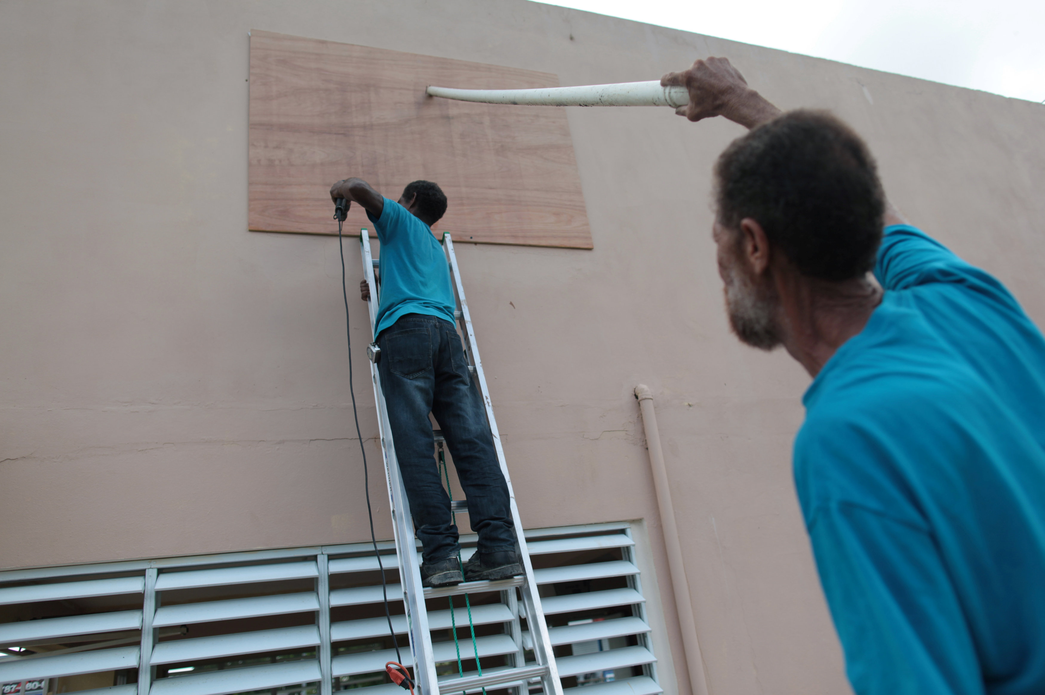 Men cover the window of a house in preparation for Hurricane Irma, in Toa Baja, Puerto Rico on Sept. 5, 2017.  (REUTERS/Alvin Baez)