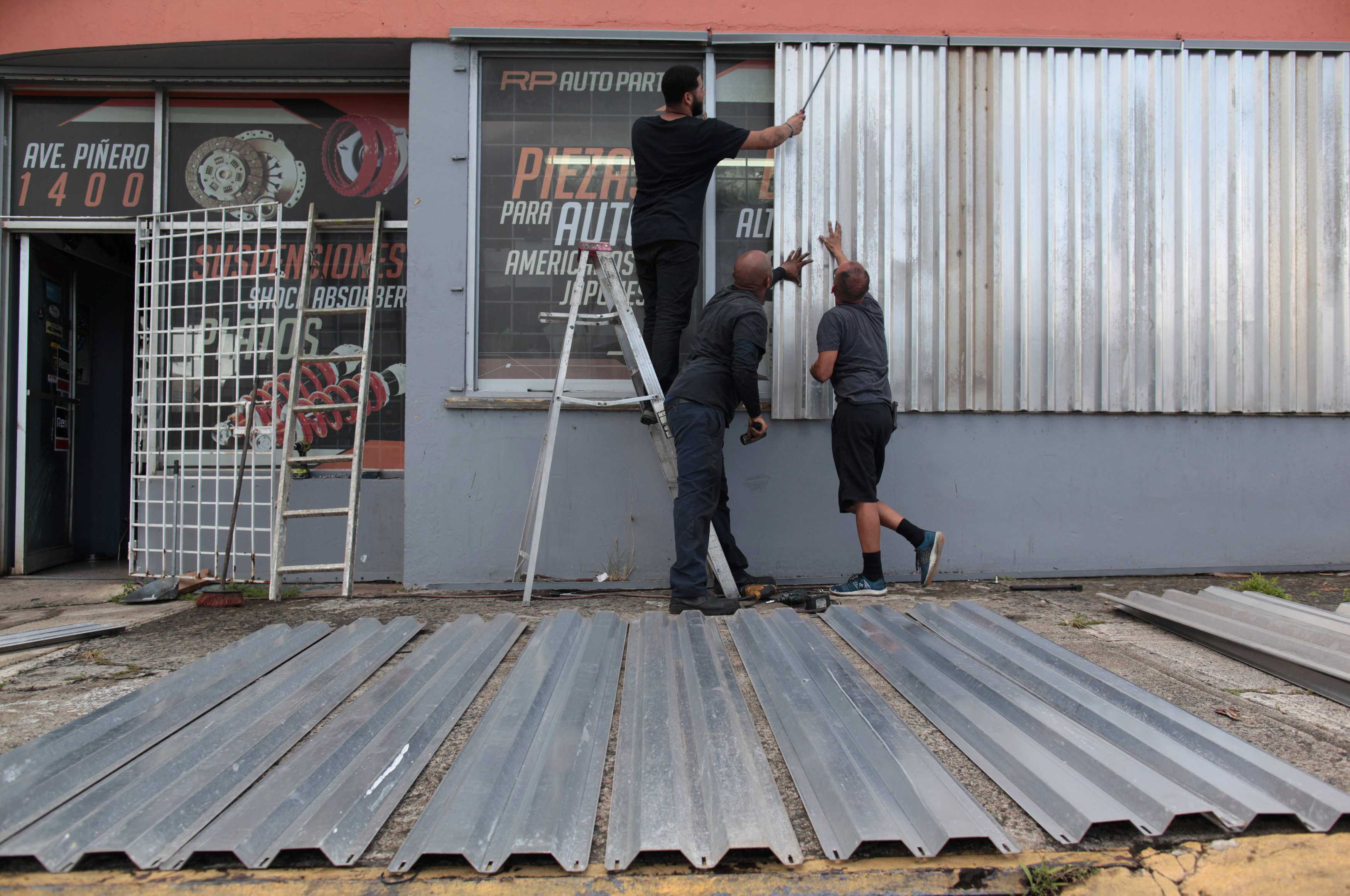 Men cover the windows of a car parts store in preparation for Hurricane Irma in San Juan, Puerto Rico on Sept. 5, 2017.  (REUTERS/Alvin Baez)