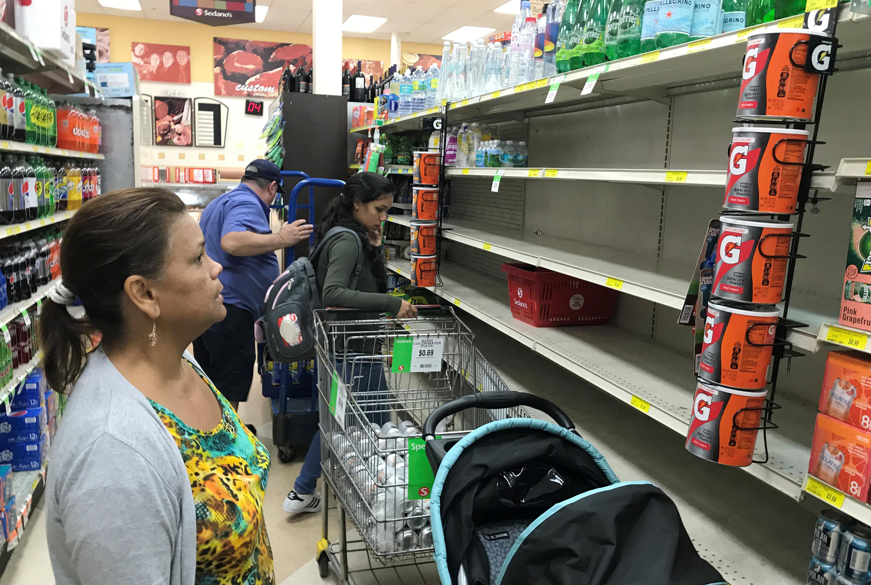A shopper in Sedano's Supermarket looks at nearly empty water shelves in the Little Havana neighborhood in Miami, Florida on Sept. 5, 2017.  (REUTERS/Joe Skipper)