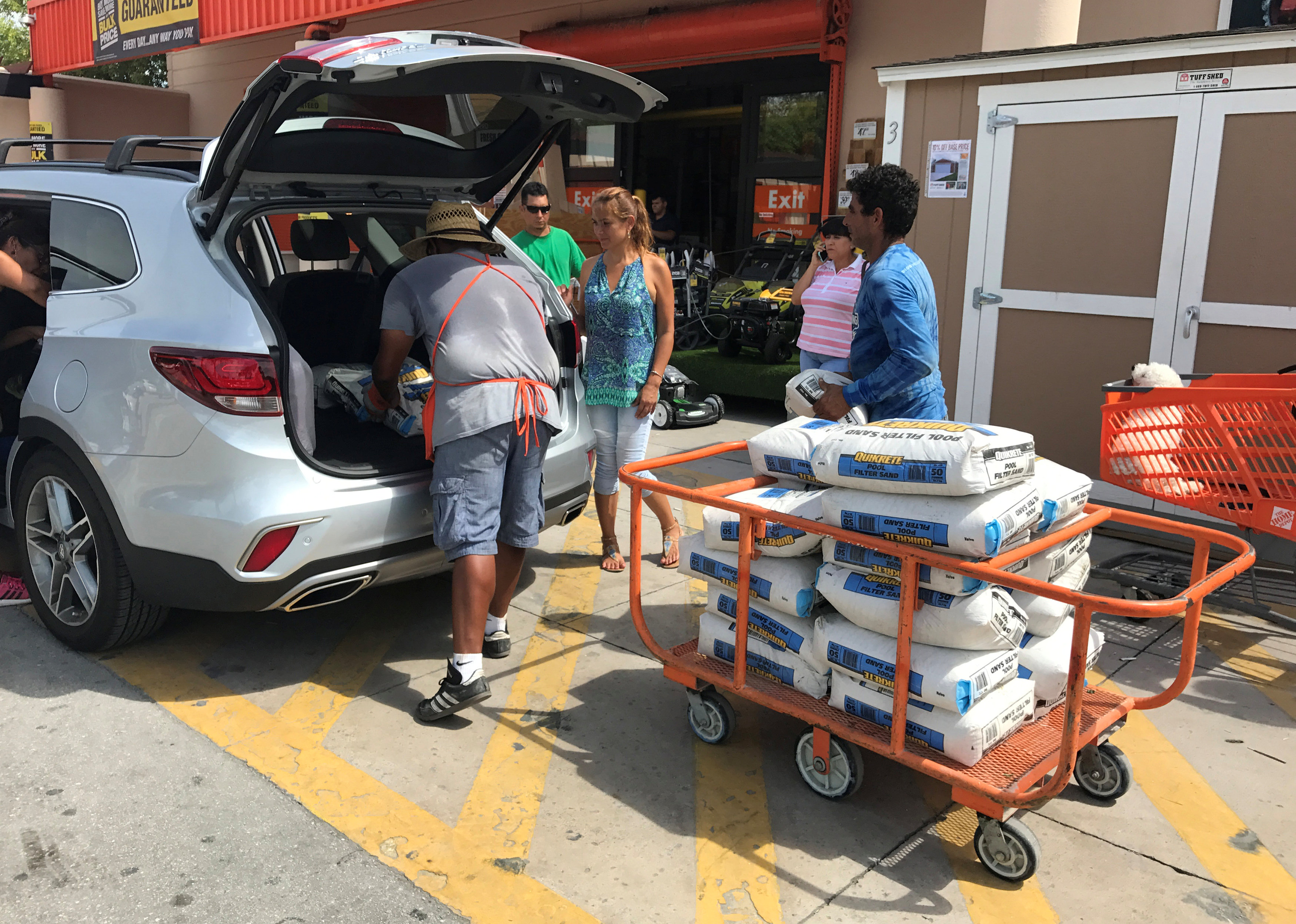 A Home Depot store employee helps to load bags of sand for customers in the Little Havana neighborhood in Miami, Florida on Sept. 5, 2017. (REUTERS/Joe Skipper)