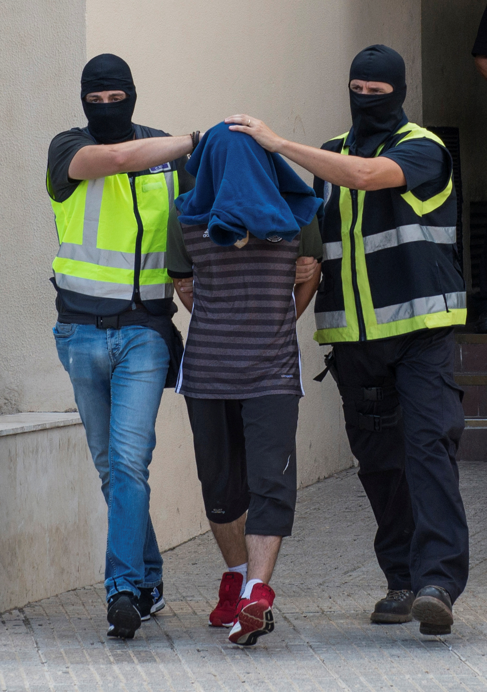 Spanish police lead a man from a police station after he was arrested for allegedly belonging to an Islamist militant cell that simulated decapitations in the Spanish north African enclave of Melilla on Sept. 6, 2017.  (REUTERS/Jesus Blasco de Avellaneda)