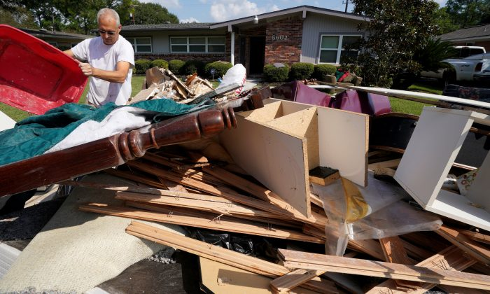 A homeowner adds to a trash pile of Hurricane Harvey flood damage in southwestern Houston, Texas on Sept. 2, 2017. (REUTERS/Rick Wilking)