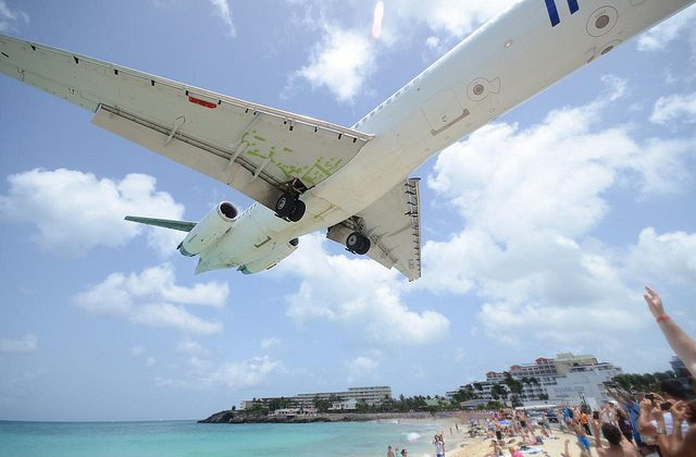 An airplane descends toward the runway at the Princess Juliana International airport as seen from Maho Beach,  St Marteen.  (Texas.713 CC BY-NC 2.0 [https://creativecommons.org/licenses/by-nc/2.0/] via Flickr)