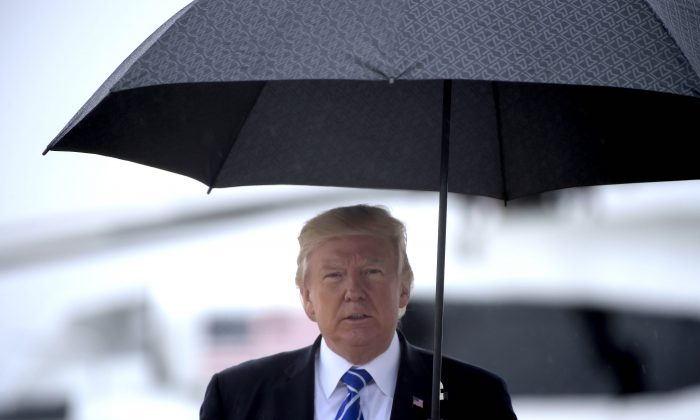 President Donald Trump walks in the rain as he departs for North Dakota from Andrews Air Force Base, Maryland, on Sept. 6, 2017. (BRENDAN SMIALOWSKI/AFP/Getty Images)