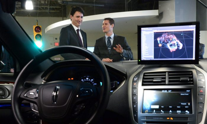 BlackberryQNXdirector of engineering Sheridan Ethier speaks to Prime Minister Justin Trudeau as he visits theBlackberryQNXfacility in Ottawa last year. (The Canadian Press/Sean Kilpatrick)