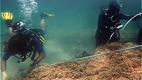 Divers sizing up the ancient Roman city of Neapolis. (Screenshot via United News International/YouTube)