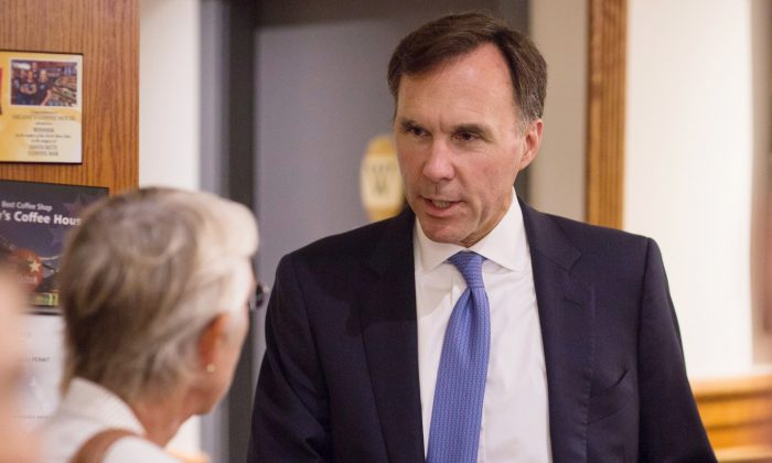 Finance Minister Bill Morneau speaks with a small business owner at a coffee shop in Vancouver on Sept. 5, 2017, before a press conference on controversial income tax reforms for small businesses. (The Canadian Press/Ben Nelms)
