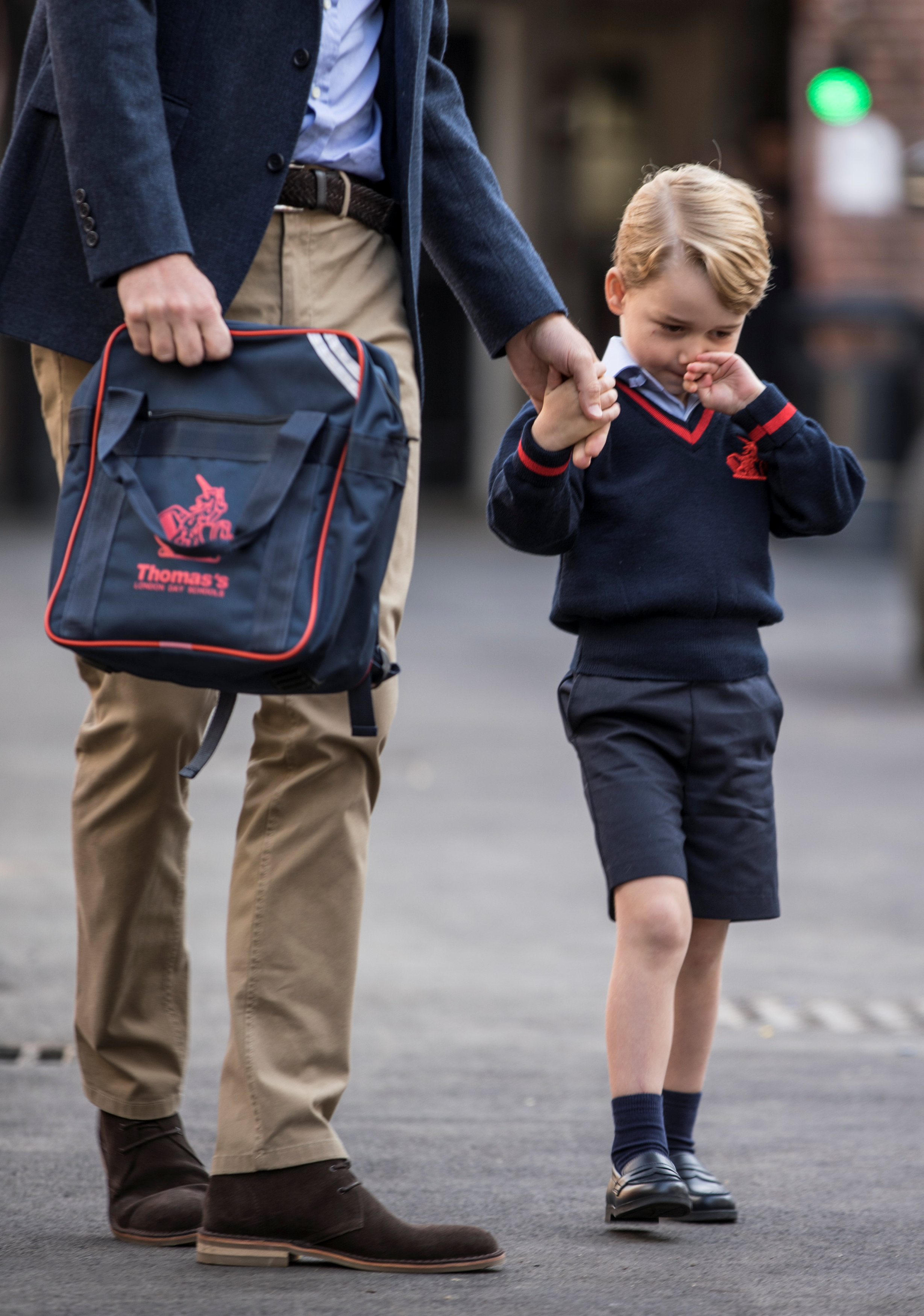 Prince George holds his father Britain's Prince William's hand as he arrives on his first day of school at Thomas's school in Battersea, London on Sept. 7, 2017. (REUTERS/Richard Pohle/Pool)