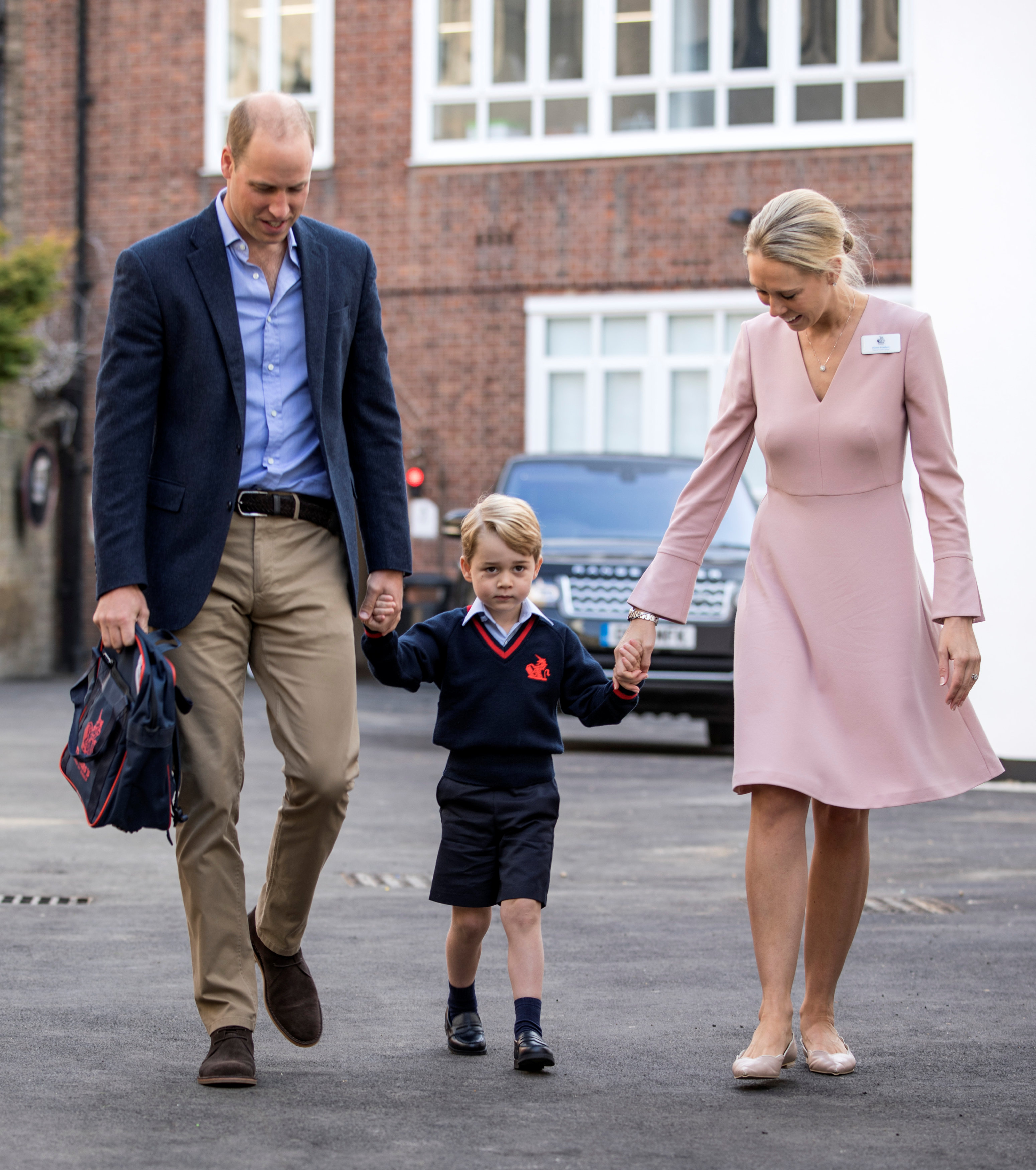 Helen Haslem, head of the lower school and Britain's Prince William hold Prince George's hands as he arrives for his first day of school at Thomas's school in Battersea, London, Sept. 7, 2017. (REUTERS/Richard Pohle/Pool)
