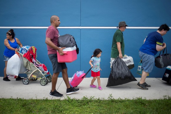 Residents carry their belongings into a shelter ahead of the downfall of Hurricane Irma in Estero, Florida, U.S. September 9, 2017. (Reuters/Adrees Latif)
