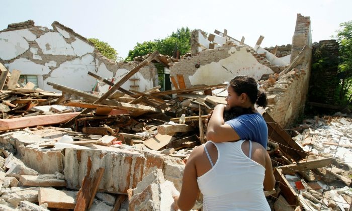 Women hug while standing next to a destroyed house after an earthquake struck the southern coast of Mexico in Union Hidalgo, Mexico on Sept.  9, 2017. (REUTERS/Jorge Luis Plata)