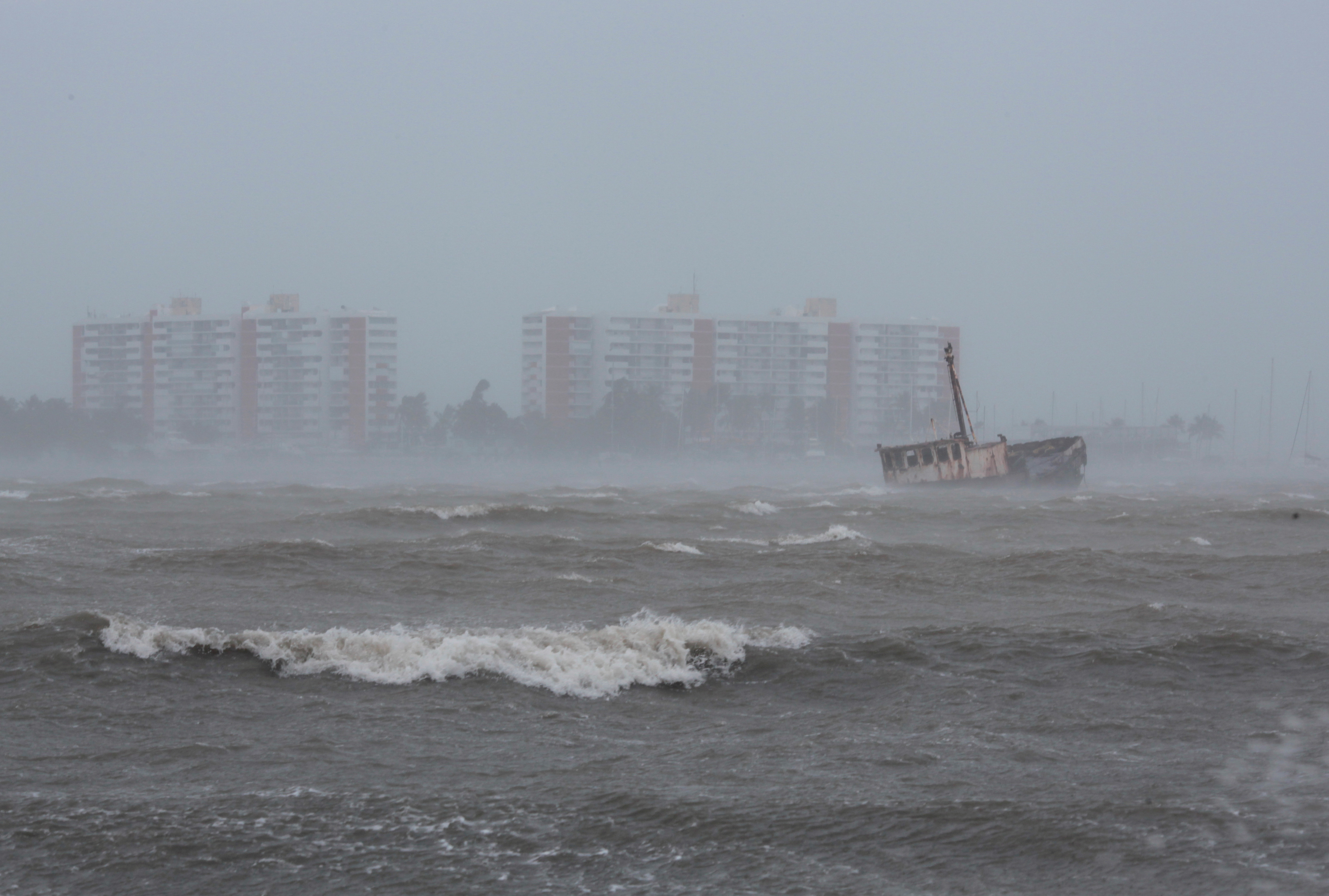 Waves battle a stranded ship in Fajardo, Puerto Rico. (REUTERS/Alvin Baez)