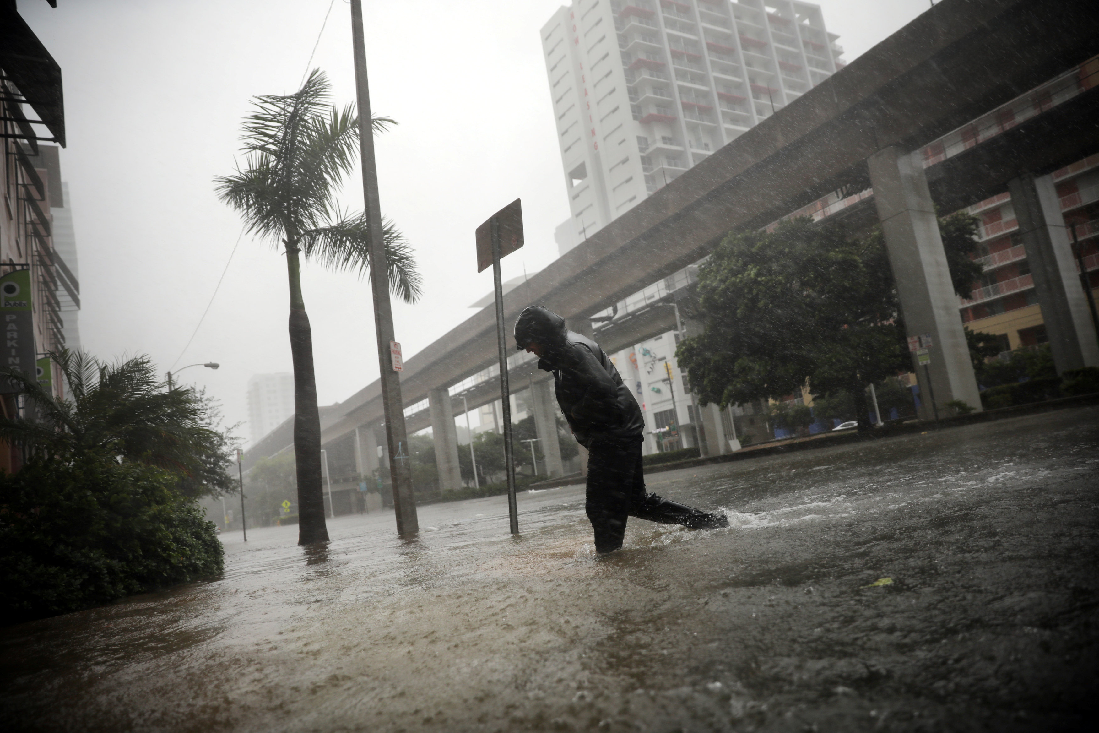 A local resident walks across a flooded street in downtown Miami as Hurricane Irma arrives at south Florida on Sept. 10, 2017. (REUTERS/Carlos Barria)