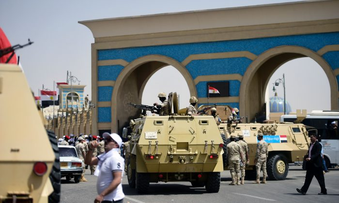 Egyptian soldiers stand guard on armoured personnel carriers, as Christian worshippers leave a stadium where Pope Francis led mass in the Egyptian capital Cairo on April 29, 2017. (KHALED DESOUKI/AFP/Getty Images)