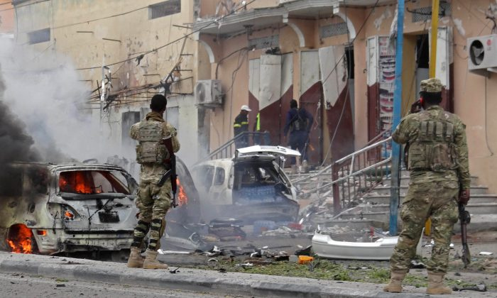 Somalian security personnel look towards burning vehicles as they secure an area in Mogadishu, after a car bomb explosion in the Somalian capital on July 30, 2017. (STR/AFP/Getty Images)