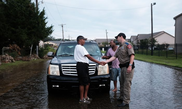ORANGE, TX - SEPTEMBER 06: Residents speak with a police officer along a flooded street in Orange as Texas slowly moves toward recovery from the devastation of Hurricane Harvey on September 6, 2017 in Orange, Texas. Almost a week after Hurricane Harvey ravaged parts of the state, some neighborhoods still remained flooded and without electricity. While downtown Houston is returning to business, thousands continue to live in shelters, hotels and other accommodations as they contemplate their future.  (Photo by Spencer Platt/Getty Images)