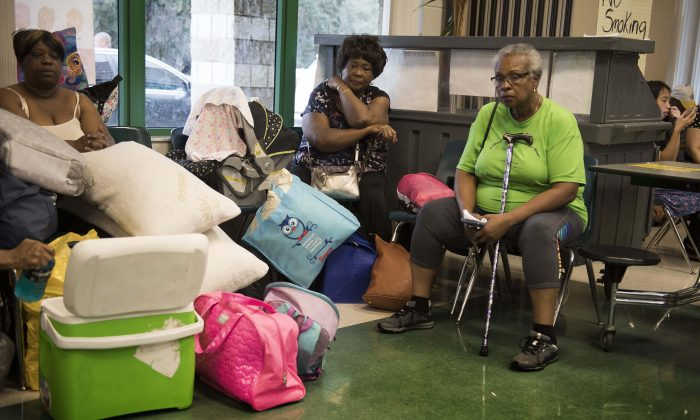 A group of women sit in the cafeteria awaiting room assignments at a shelter within the Pizzo Elementary School in Tampa, Florida where Tampa residents are fleeing the evacuation zones ahead of Hurricane Irma's landfall Sept. 9, 2017. (JIM WATSON/AFP/Getty Images)