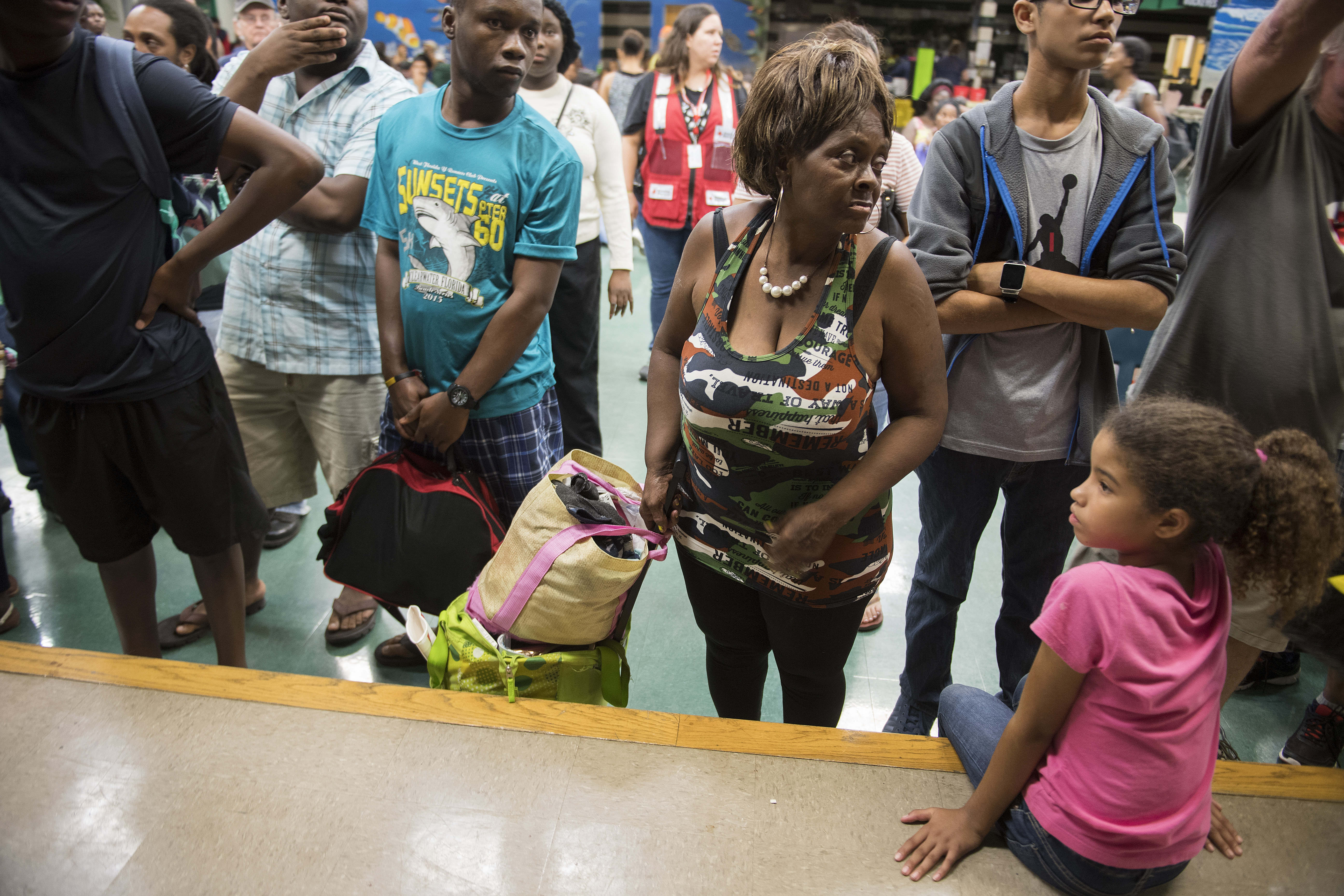 A group of people wait in the cafeteria for room assignments at a shelter within the Pizzo Elementary School in Tampa, Florida where Tampa residents are fleeing the evacuation zones ahead of Hurricane Irma's landfall on Sept. 9, 2017. (JIM WATSON/AFP/Getty Images)