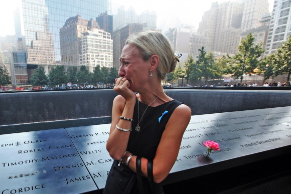 NEW YORK, NY - SEPTEMBER 11: Carrie Bergonia of Pennsylvania looks over the name of her fiance, firefighter Joseph Ogren at the 9/11 Memorial during ceremonies for the twelfth anniversary of the terrorist attacks on lower Manhattan at the World Trade Center site on September 11, 2013 in New York City. The nation is commemorating the anniversary of the 2001 attacks which resulted in the deaths of nearly 3,000 people after two hijacked planes crashed into the World Trade Center, one into the Pentagon in Arlington, Virginia and one crash landed in Shanksville, Pennsylvania. Following the attacks in New York, the former location of the Twin Towers has been turned into the National September 11 Memorial & Museum. (Photo by Chris Pedota-Pool/Getty Images)