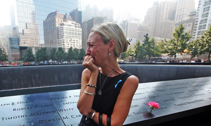 Carrie Bergonia of Pennsylvania looks over the name of her fiance, firefighter Joseph Ogren at the 9/11 Memorial during ceremonies for the twelfth anniversary of the terrorist attacks on lower Manhattan at the World Trade Center site on September 11, 2013 in New York City. The nation is commemorating the anniversary of the 2001 attacks which resulted in the deaths of nearly 3,000 people after two hijacked planes crashed into the World Trade Center, one into the Pentagon in Arlington, Virginia and one crash landed in Shanksville, Pennsylvania. Following the attacks in New York, the former location of the Twin Towers has been turned into the National September 11 Memorial & Museum.  (Photo by Chris Pedota-Pool/Getty Images)