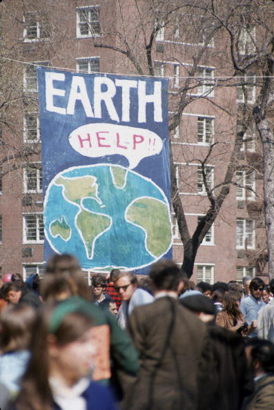 People gather near a large poster that shows a speech bubble from planet Earth that reads 'Help!!', on the occasion of the first Earth Day conservation awareness celebration, New York City, on April 22, 1970. (Hulton Archive/Getty Images)