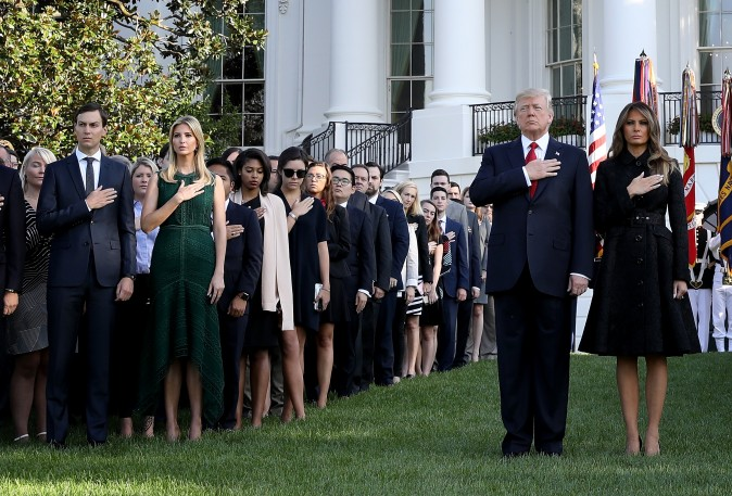 "WASHINGTON, DC - SEPTEMBER 11: U.S. President Donald Trump and first lady Melania Trump, flanked by White House staff, place their hands over their hearts on the South Lawn of the White House during the playing of ""Taps"" at a ceremony marking the September 11 attacks September 11, 2017 in Washington, DC. Today marks the 16th anniversary of the attacks that killed almost 3,000 people and wounded another 6,000. Also pictured are Trump's daughter Ivanka Trump (2nd L) and Jared Kushner (L). (Photo by Win McNamee/Getty Images)"